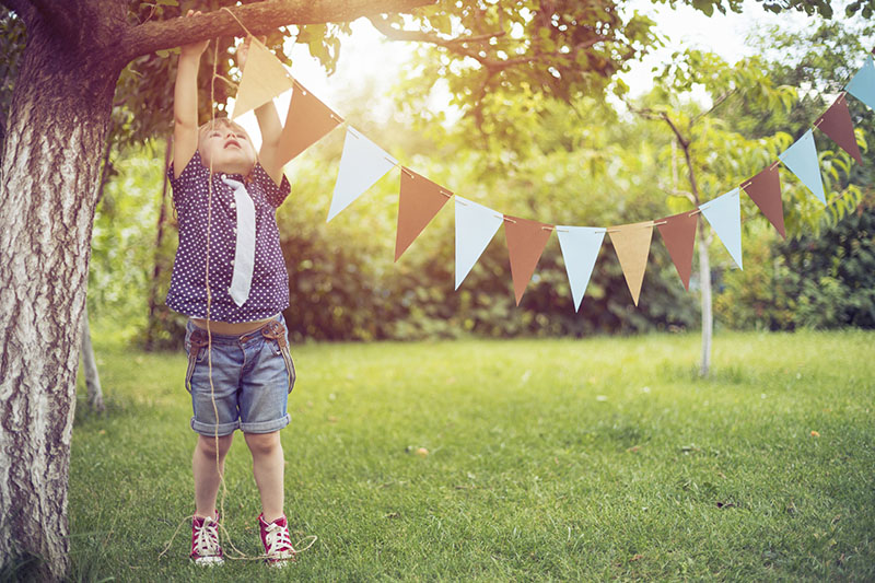 Kid Hanging a Garland for a Celebration